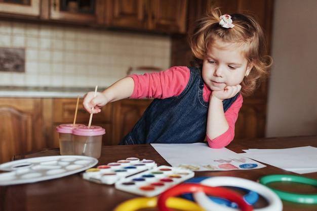 Cute little girl draws a circle of colored paints