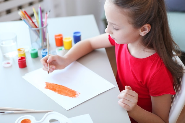 Cute little girl draws paints at home