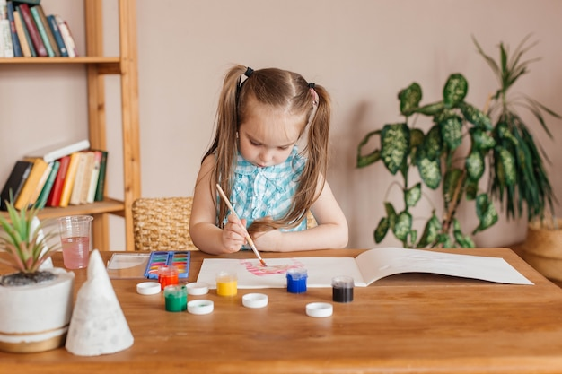 Милая маленькая девочка рисует кистью и красками за столом в гостиной