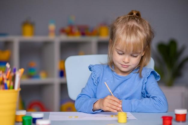 Милая маленькая девочка рисует красками в детском саду