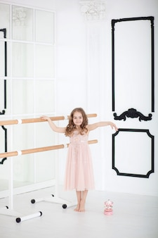 Cute little girl dreams of becoming a ballerina. child girl in pink dress dancing in room. baby girl is studying ballet.  little girl holding a musical toy carousel.  indoors ballet hall class room
