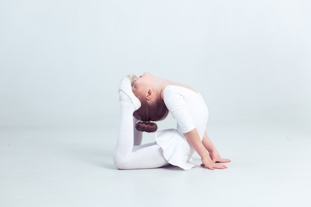 Cute little girl dreams of becoming a ballerina child girl in a white dancewear dancing