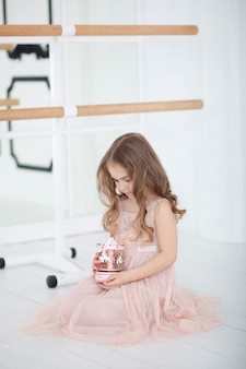 Cute little girl dreams of becoming a ballerina. little ballerina in dress sits in a dance class on floor. baby girl is studying ballet. little girl holding toy carousel. vintage musical carousel toy.