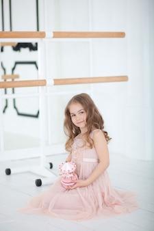 Cute little girl dreams of becoming a ballerina. little ballerina in dress sits in a dance class on floor. girl is studying ballet. little girl holding a musical toy carousel. ballet hall class