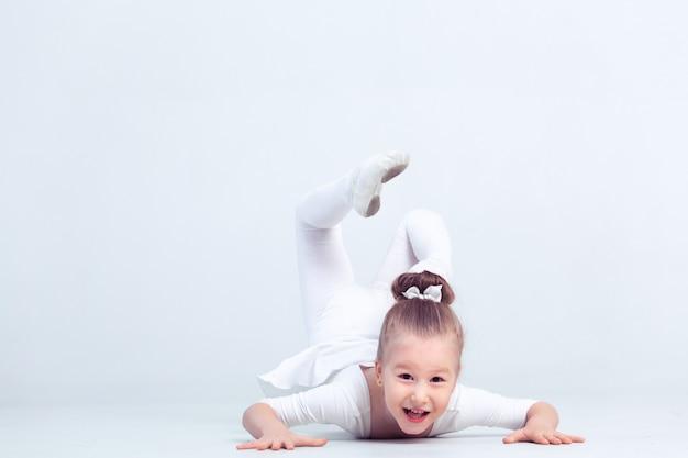 Милая маленькая девочка мечтает стать балериной. девочка в белой танцевальной одежде танцует.