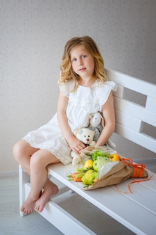 かわいい女の子はお姫様になることを夢見ています。白いインテリア、花とおもちゃの明るい子供部屋