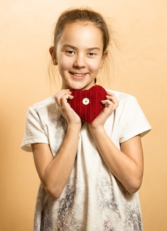 Cute little girl in dress posing with red knitted heart