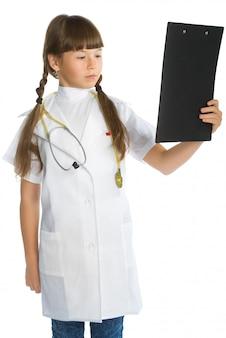 Милая маленькая девочка в костюме врача, держащего буфер обмена