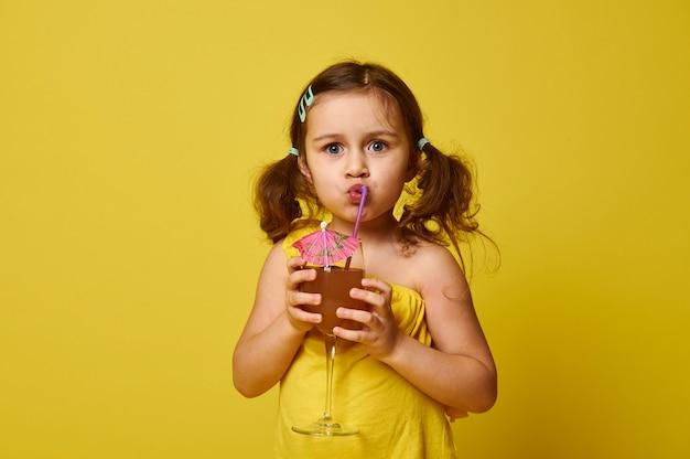 コピースペースで黄色に分離されたストローからトロピカルフルーツカクテルを飲むかわいい女の子。