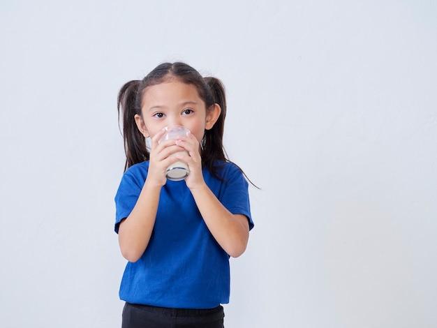 Cute little girl drinking milk from glass on light