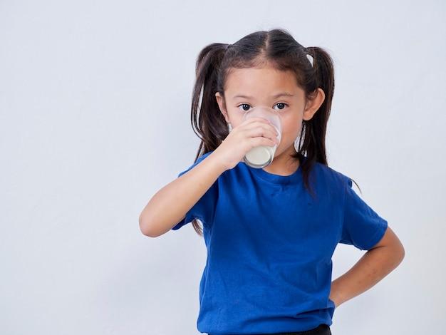 光のガラスからミルクを飲むかわいい女の子
