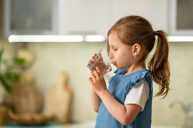 Милая питьевая вода маленькой девочки в кухне дома. водный баланс.