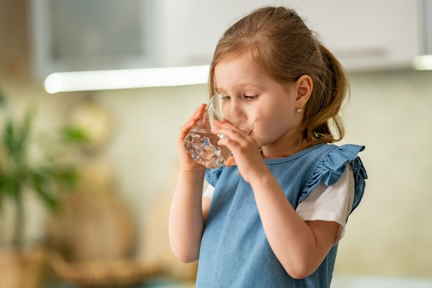 Cute little girl drinking water in kitchen at home. water balance.