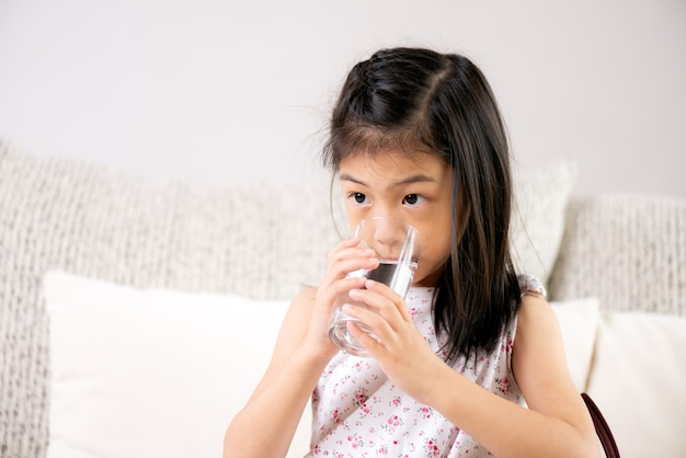 Cute little girl drinking water on sofa at home. health care concept