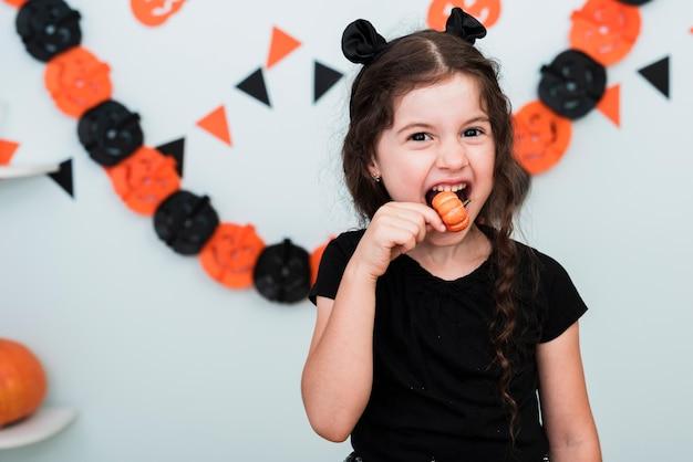 Милая маленькая девочка ест конфеты
