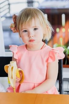 Милая маленькая девочка ест банан