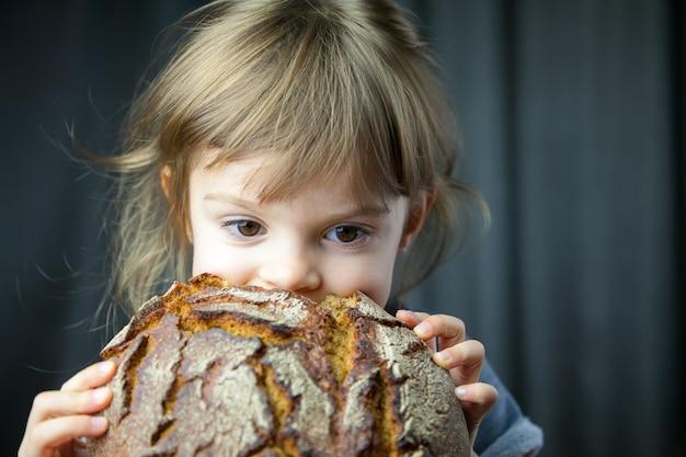 Cute little girl eating a big crunchy circle rye bread, she's very hungry