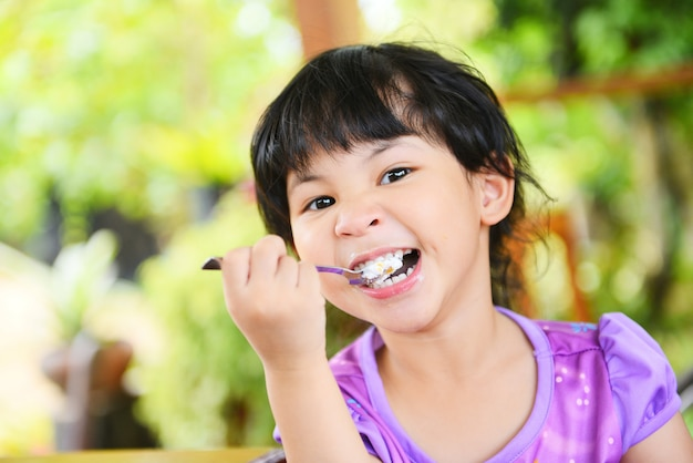 Cute little girl eating cake. asian child happy and holding a spoon into the mouth with cake on dining table , selective focus