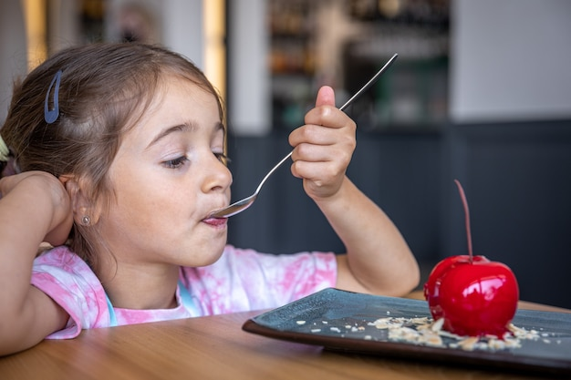 Cute little girl eating cherry-shaped chocolate mousse, french dessert with biscuit base, icing and fruit filling.