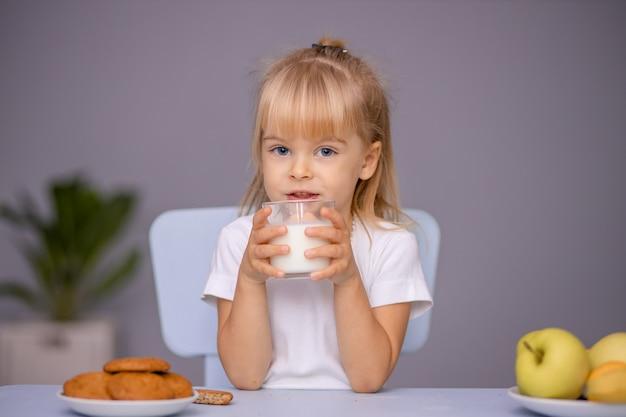 쿠키를 먹고 집이나 유치원에서 우유를 마시는 귀여운 소녀