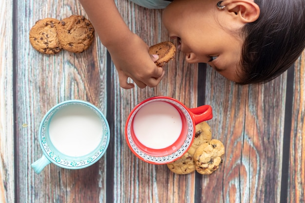 Cute little girl eating cookies with milk