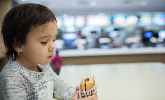 Cute little girl eating a hamburger in the fast food