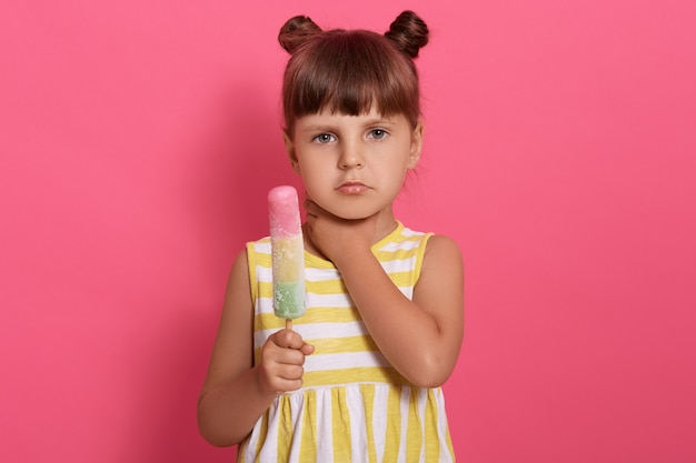Cute little girl eating ice cream and has sore throat