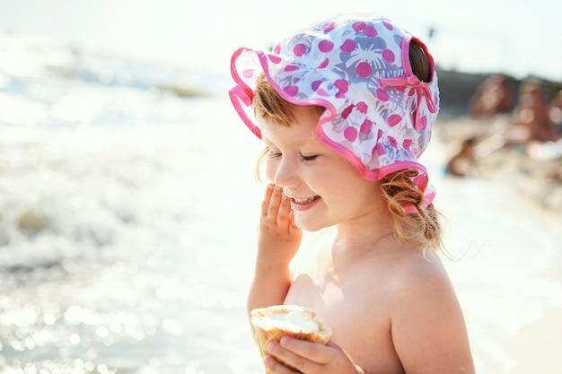 해변 휴가에 아이스크림을 먹는 귀여운 소녀