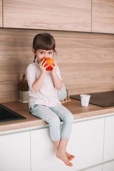 부엌 표면에 앉아 달콤한 빨간 사과 먹는 귀여운 작은 소녀. 건강한 먹는 개념.
