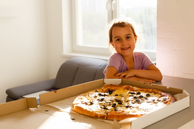 Cute little girl eating pizza at home