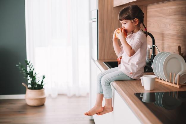 부엌 표면에 앉아 빨간 사과 먹는 귀여운 작은 소녀. 건강한 먹는 개념.