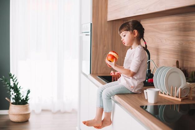 부엌에 앉아 붉은 육즙 사과 먹는 귀여운 작은 소녀. 건강한 먹는 개념.