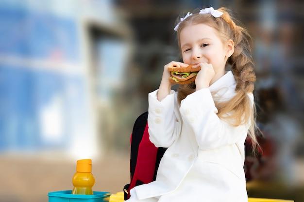 Милая маленькая девочка ест бутерброд во время перерыва между занятиями. здоровое нездоровое питание для малыша. завтрак обед для детей в школе.