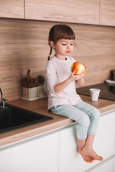 부엌 표면에 앉아 맛있는 붉은 육즙 사과 먹는 귀여운 소녀. 건강한 먹는 개념.