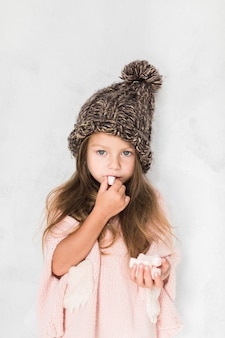 Cute little girl eating and wearing winter hat