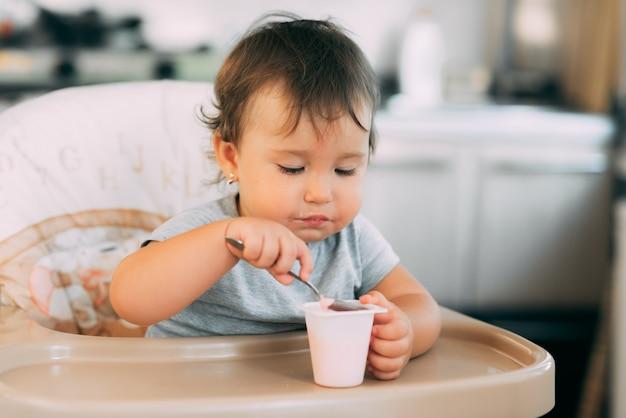 高い椅子で日中にキッチンでヨーグルトを食べるかわいい、小さな女の子