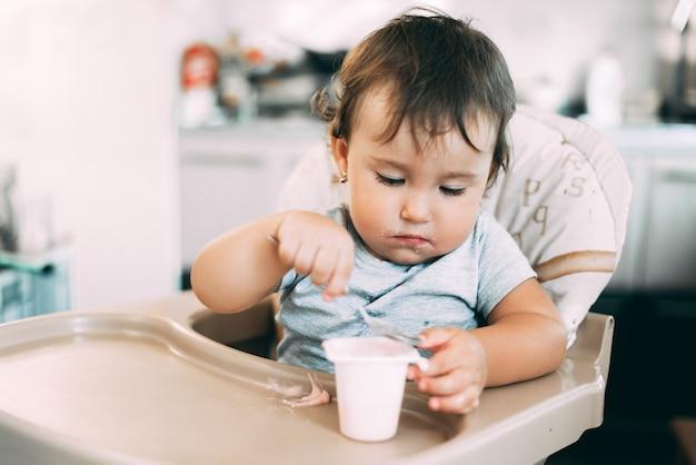 高い椅子で日中にキッチンでヨーグルトを食べるかわいい、小さな女の子 Premium写真