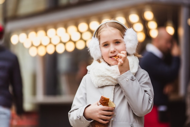 A cute little girl eats a traditional hungarian sweet pastry on the street market at wintertime