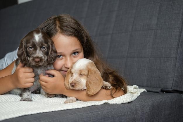 Милая маленькая девочка обнимает и лежит с двумя щенками русского спаниеля под на диване. уход за домашними животными и дружелюбная концепция. любовь и дружба между человеком и животным.