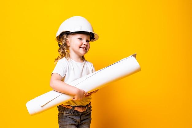 Симпатичная маленькая девочка-инженер в шлеме, держащая чертеж, изолированный на желтой стене