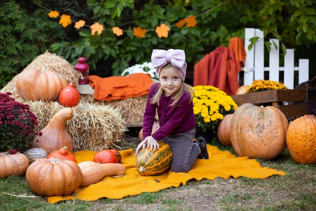 Cute little girl enjoying harvest festival celebration with pumpkins