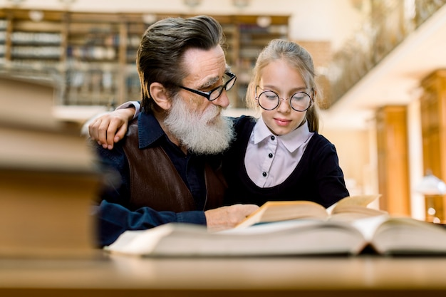 Cute little girl in eyeglasses sitting at the table in ancient library, hugging her grandfather
