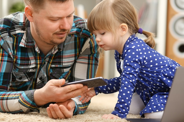 Cute little girl on floor carpet with dad use cellphone calling mom portrait. life style apps social web network wireless ip telephony concept