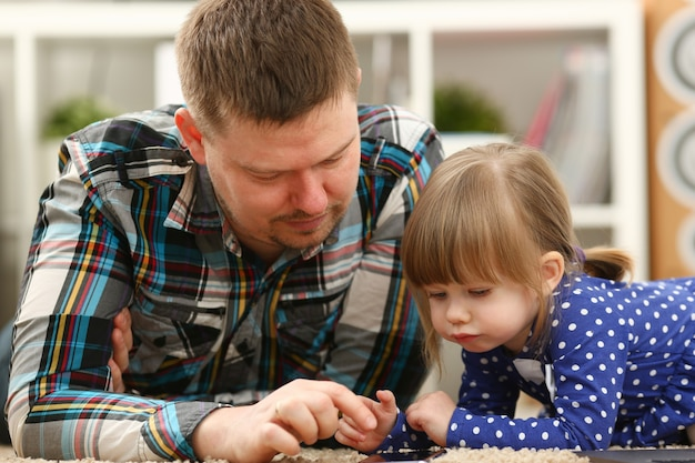 Cute little girl on floor carpet with dad use cellphone calling mom portrait