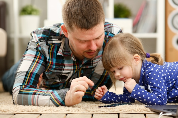 Cute little girl on floor carpet with dad