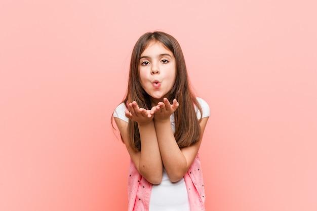 공기 키스를 보내 입술을 접고 손바닥을 들고 귀여운 소녀.