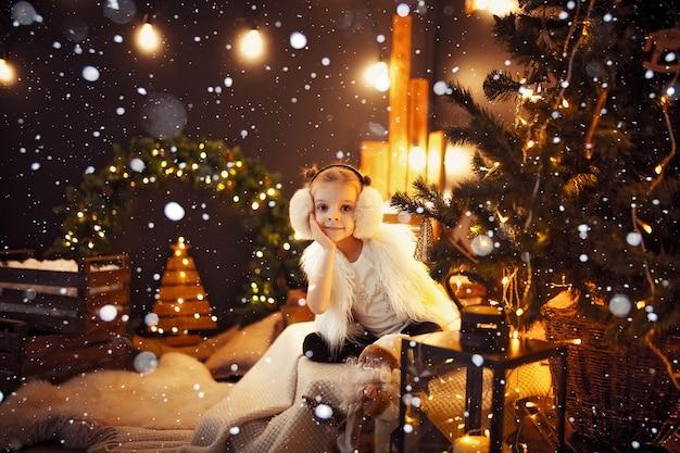 Cute little girl in fur earmuffs sitting near christmas tree