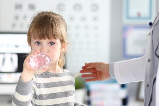 医者のオフィスで水を得るかわいい女の子