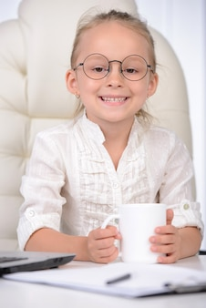 Cute little girl in glasses and formalwear sitting at table.