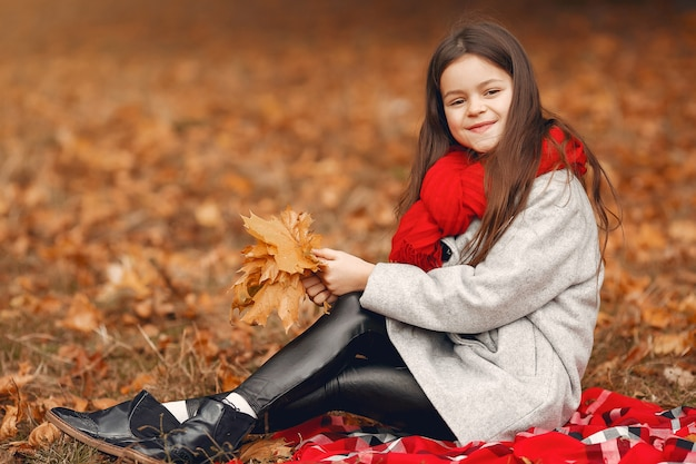 Cute little girl in a gray coat playing in a autumn park